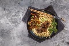 Nudelnudlar för traditionell kines med stekt kött och sallad i en porslinplatta på en grå tabell royaltyfri foto