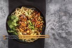 Nudelnudlar för traditionell kines med stekt kött och sallad i en porslinplatta på en grå tabell arkivfoto