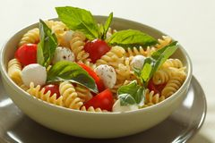 Nudelsalat mit Kirschtomaten und Basilikumblättern Stockfotos