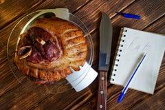 Nudillo frito del cerdo en una placa transparente en la escala de la cocina Cuenta de calor?as, de las prote?nas, de las grasas y foto de archivo