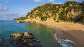 Nudist beach in Spain, Cala sa Boadella, Costa Brava, Lloret de Mar. Sandy spanish beach with rocks and stones in water. Rocky mediterranean bay Royalty Free Stock Images