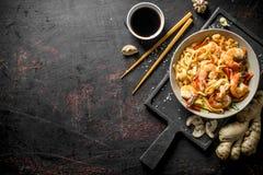 Nudlar i en platta på en skärbräda med ingefäran och soya royaltyfri bild