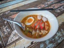 Nudlar i thailändsk kryddig tom yum soppa med rött griskött royaltyfri bild