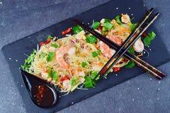 Nudlar med räkor och grönsaker på en svart stenplatta med traditionell orientalisk sås på en grå färg gör sammandrag bakgrund fotografering för bildbyråer