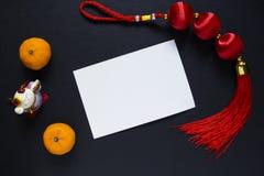 Nudo chino y mandarinas del Año Nuevo en fondo negro con la postal en blanco Imagen de archivo