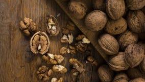 Nueces agrietadas y enteras en la tabla de madera Fotos de archivo libres de regalías