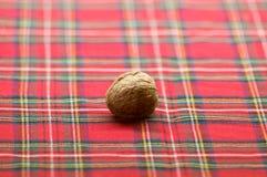 Nueces, almendras, avellanas, nueces del cacahuete en el fondo a cuadros rojo blanco de la tela Imagen de archivo