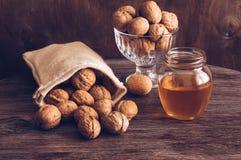 Nueces con la miel en la tabla Nueces en una bolsa de la lona Fotografía de archivo libre de regalías