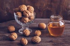 Nueces con la miel Nueces con la miel en una tabla de madera Tono hermoso Imagen de archivo