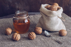 Nueces con la miel Nueces en un bolso de la lona y miel en un tarro Tabla de madera con la servilleta de lino Foto de archivo