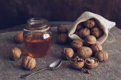 Nueces con la miel Nueces en un bolso de la lona y miel en un tarro Tabla de madera con la servilleta de lino Foto de archivo libre de regalías