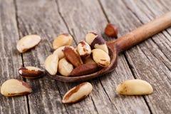 Nueces de Brasil en una cuchara en fondo de madera Imagen de archivo libre de regalías