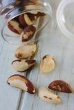 Nueces de Brasil y botella de cristal sobre la tabla blanca Fotografía de archivo libre de regalías