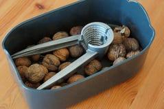 Nueces de Brown en una caja negra con una herramienta gris del metal foto de archivo libre de regalías
