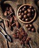 Nueces de la macadamia, de la pacana y de Pili en la tabla de madera Foto de archivo