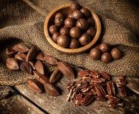 Nueces de la macadamia, de la pacana y de Pili en la tabla de madera Imágenes de archivo libres de regalías