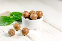 Nueces de macadamia agradables en la tabla de madera blanca Fotos de archivo