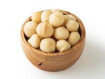 Nueces de macadamia en cuenco de madera fotos de archivo