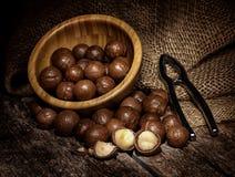 Nueces de macadamia en la tabla de madera Fotos de archivo libres de regalías