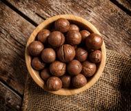 Nueces de macadamia en la tabla de madera Imagen de archivo libre de regalías