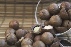 Nueces de macadamia en un vidrio en una superficie de madera Imagen de archivo