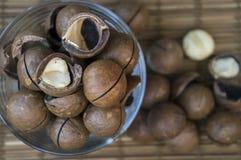 Nueces de macadamia en un vidrio en una superficie de madera Fotografía de archivo