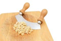 Nueces de macadamia grueso tajadas con un cuchillo oscilante Foto de archivo