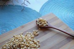 Nueces de pino con una cuchara de madera en top-vista fotos de archivo