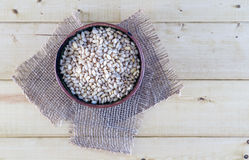 Nueces de pino en cuenco de la cerámica en fondo rústico Foto de archivo libre de regalías