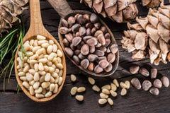 Nueces de pino en el cono de la nuez de la cuchara y de pino en la tabla de madera Alimento biológico imagenes de archivo