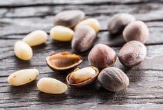 Nueces de pino en la tabla de madera oscura Alimento biológico Macro fotos de archivo libres de regalías