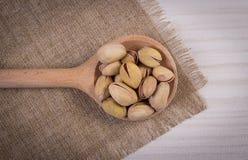 Nueces de pistacho con la cuchara en la tabla de madera blanca, consumición sana Foto de archivo