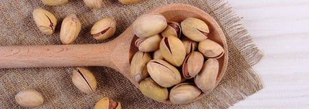 Nueces de pistacho con la cuchara en la tabla de madera blanca, consumición sana Imagen de archivo