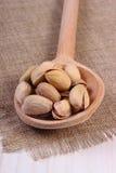 Nueces de pistacho con la cuchara en la tabla de madera blanca, consumición sana Fotos de archivo libres de regalías
