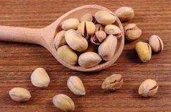 Nueces de pistacho con la cuchara en la tabla de madera, consumición sana Imagenes de archivo