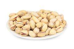 Nueces de pistacho deliciosas en la placa en el fondo blanco Fotografía de archivo libre de regalías