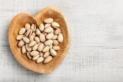 Nueces de pistacho en cuenco de madera en forma de corazón en fondo de madera foto de archivo