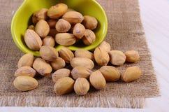 Nueces de pistacho en cuenco en la tabla de madera blanca, consumición sana Fotos de archivo