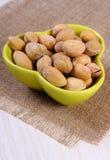 Nueces de pistacho en cuenco en la tabla de madera blanca, consumición sana Imagen de archivo libre de regalías