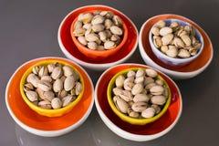 Nueces de pistacho en cuencos atractivos de la porcelana fotos de archivo libres de regalías