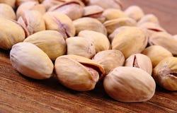 Nueces de pistacho en el tablero de madera, consumición sana fotos de archivo