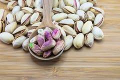 Nueces de pistacho en la cuchara de madera en el fondo de madera Imagen de archivo libre de regalías