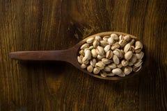 Nueces de pistacho en la cuchara de madera en el fondo de madera Fotos de archivo