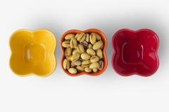 Nueces de pistacho en los cuencos coloridos fotos de archivo libres de regalías