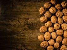 Nueces dispersadas en una tabla de madera fotografía de archivo