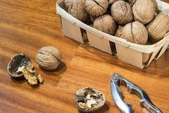 Nueces en cesta de mimbre con el cascanueces Fotos de archivo libres de regalías