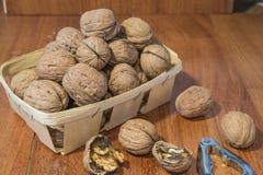 Nueces en cesta de mimbre con el fondo de madera Foto de archivo libre de regalías