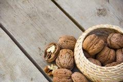 Nueces en la cesta en la textura de madera del fondo Fotos de archivo libres de regalías