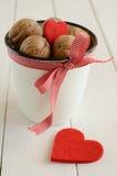 Nueces en la taza blanca y dos corazones rojos Foto de archivo