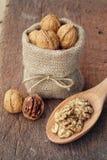 Nueces enteras en corazones del bolso y de la nuez de la harpillera en la cuchara de madera Foto de archivo